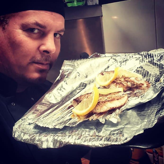 chef Lesley in zijn keuken met verse kabeljauw, gebakken in roomboter.
